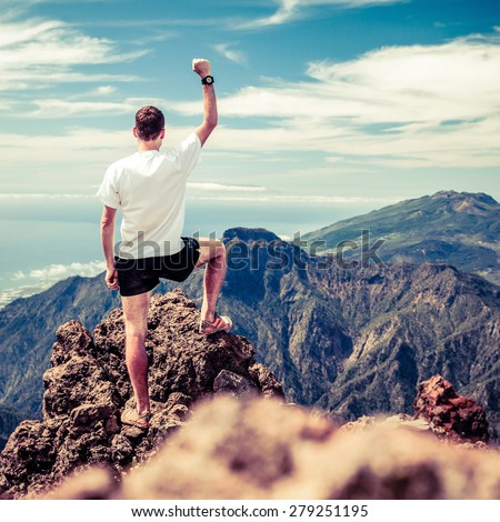 Trail runner, man and success accomplish in mountains. Motivation and inspiration on mountains peak. Running, sports, fitness and healthy lifestyle outdoors in summer nature - stock photo