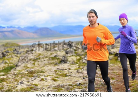 Trail runner man and woman running cross-country run training outside for marathon. Jogging male athlete working out as part of healthy lifestyle. Image from Snaefellsnes, Iceland. - stock photo