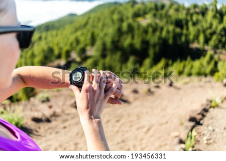 Trail runner or hiker on mountain path looking at sportwatch, checking performance or heart pulse,heart monitor. Cross country running in beautiful nature,Canary Islands. Sport and exercising outdoors - stock photo