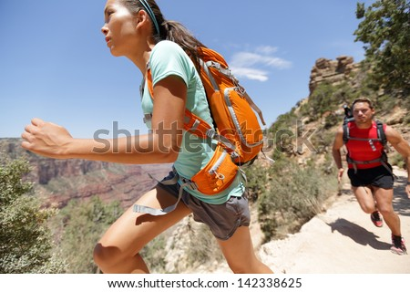 Trail runner woman in cross country running race in Grand Canyon. Couple training working out together sprinting fast at speed in beautiful landscape nature in Grand Canyon, Arizona, USA. - stock photo