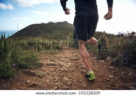 trail running athlete exercising for fitness and health outdoors on mountain pathway - stock photo