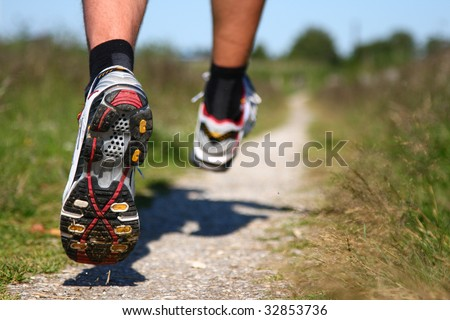 Trail running. Freeze action closeup of running shoes in action. Shallow depth of field, focus on left shoe. - stock photo