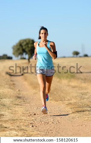 Trail running in country side path. Woman runner exercising and training for cross race. Fitness girl on summer rural landscape. - stock photo