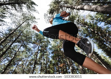 trail running jump fitness woman training alone outdoors in the forest - stock photo