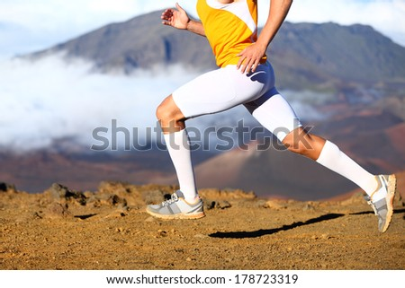 Trail running - male runner in cross country run. Closeup of strong legs and running shoes sprinting at speed. Male athlete fitness runner in compression sports clothing, socks and shorts. - stock photo
