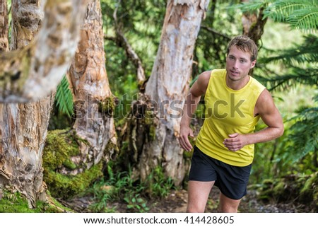 Trail running man athlete runner in forest nature path jogging along trees in summer landscape. Male sports fitness fit guy training hard exercising sweating living a healthy and active life. - stock photo