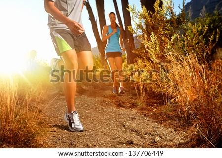Trail running marathon athlete outdoors sunrise couple training for fitness and healthy lifestyle - stock photo
