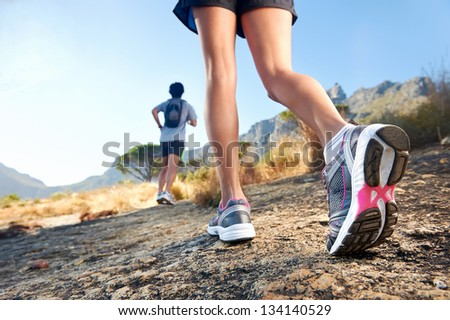 trail running marathon fitness feet on rock fitness and healthy lifestyle - stock photo
