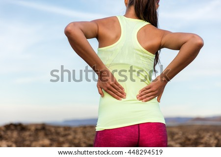 Trail running runner with painful lower back pain injury or strained muscle near the spine. Female athlete from behind on outdoor run pressing body with hands for muscles cramping soreness. - stock photo