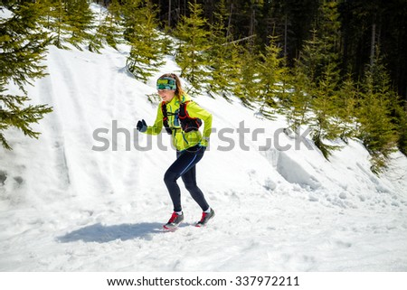 Trail running woman runner in winter mountains on snow. Motivation and inspiration fitness concept with beautiful inspirational landscape. Active accomplish runner or hiker power walking in nature. - stock photo