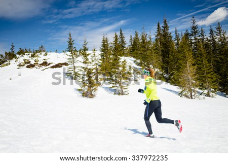 Trail running woman runner in winter mountains on snow. Motivation and inspiration fitness concept with beautiful inspirational landscape. Active accomplish runner power walking outdoors in nature. - stock photo
