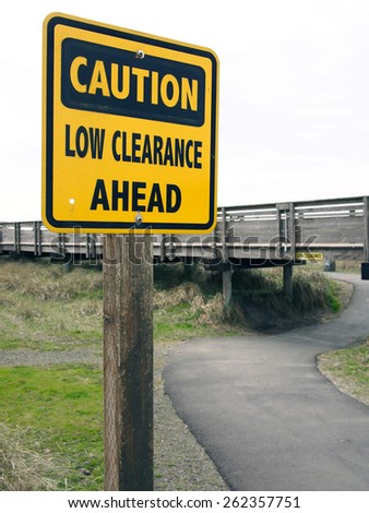 Trail sign warns with a clearance warning.
