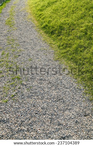 Trail with pebble and green grass - stock photo