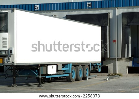Trailer of truck sitting at a loading dock. - stock photo