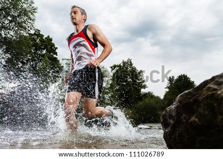 trailrunner with splashing water - stock photo