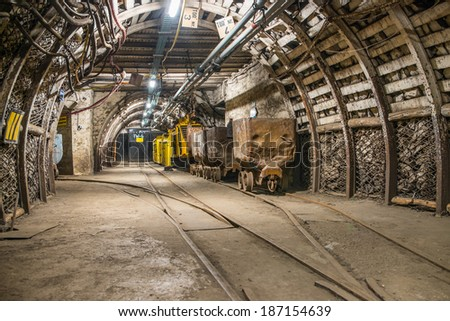 Train and carts in coal mine - stock photo