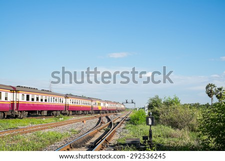 Train and line of multiple railway tracks crossing in rural of Thailand with white cloud and blue sky background - stock photo