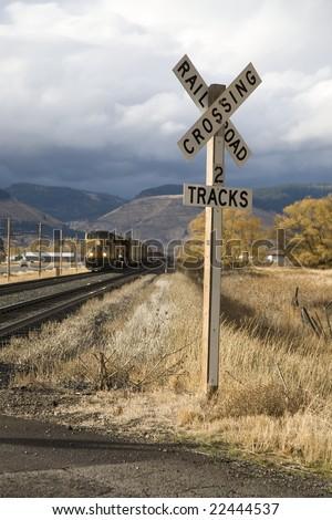 train approaching a rural crossing - stock photo
