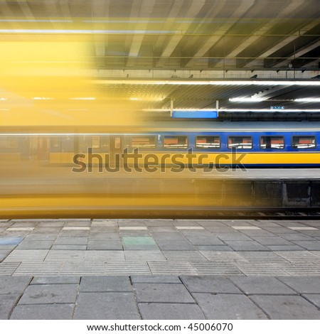 Train arriving at a platform, leaving a blur and a glimpse on a waiting train on another platform