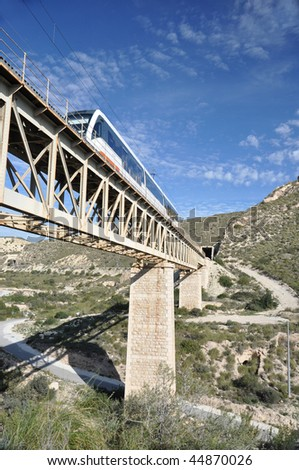 Train crossing bridge in the mountains of Spain under a blue sky