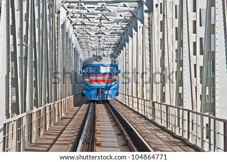 train crossing the river on an iron bridge - stock photo