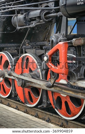 Train drive mechanism and red wheels of an old soviet steam locomotive - stock photo