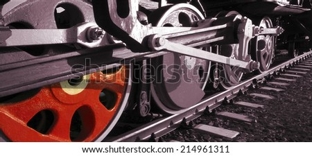 Train drive mechanism and red wheels of an old soviet steam locomotive. Grunge - stock photo