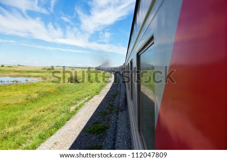 Train goes by rail in summer day, countryside. - stock photo