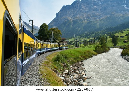 Train heading up the mountains next to a mountain river - stock photo
