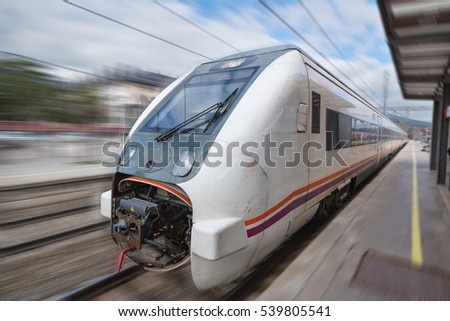 Train in motion with blurred background arriving at the station