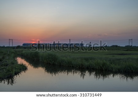 train in sunset, The Netherlands - stock photo