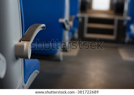 Train inside with blue seats and lots of empty space