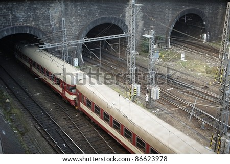 Train is leaving from railroad station to tunnel - blurred motion - stock photo