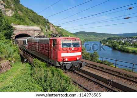 Train leaving a tunnel near the river Moselle in Germany - stock photo