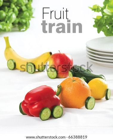 Train made of various fruit on white table cloth - stock photo