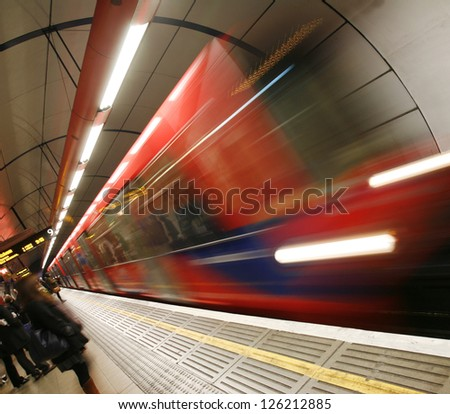 Train, motion blurred, passing through a DLR, Docklands Light Railway, station and people are present at platform, - stock photo