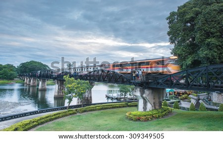 Train moving across River Kwai Bridge (WWII historical building), Kanchanaburi, Thailand at the evening