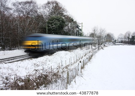 train on railway tracks with motion blur in snowy landscape