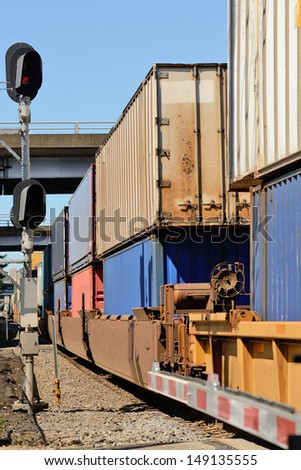 Train passes through an industrial section of a large northwest american city with intermodal modular shipping containers - stock photo