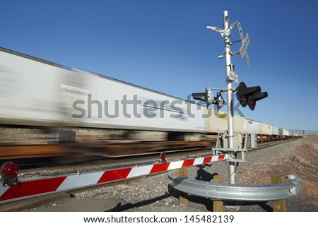 Train passing level crossing motion blur - stock photo