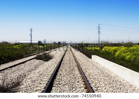 train rails with a city at the background - stock photo
