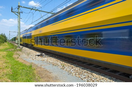 Train riding through the countryside in spring - stock photo