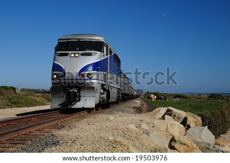 train rushes along tracks on the California coast - stock photo
