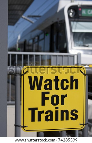 Train sign with train departing in the background - stock photo