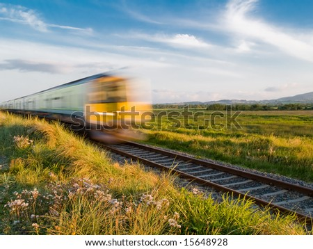 Train speeding through Irish village in the afternoon sunlight - stock photo