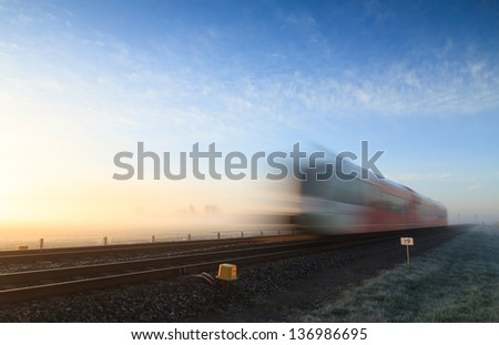 Train speeding through the landscape during foggy sunrise at spring. - stock photo