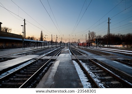 Train station in cold winter at sunset with freight train - stock photo