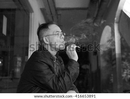 Train station, Nakhornratchasima Province,Thailand April  28 2016: Portrait old man smoking  cigarette.Wait for the train at the station in time ranges national labor day Festival.Black - white color