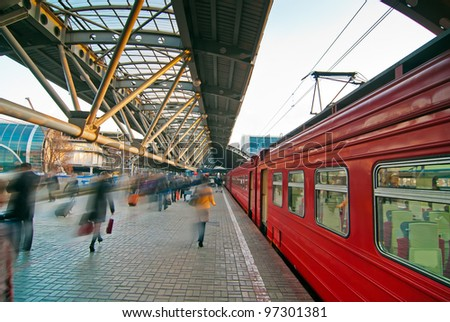 Train station with red train and  blurred people. - stock photo