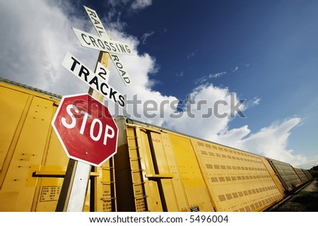 Train stopped at a crossing with a dramatic sky. - stock photo